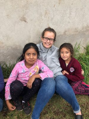 Volunteer sitting with children in Guatemala